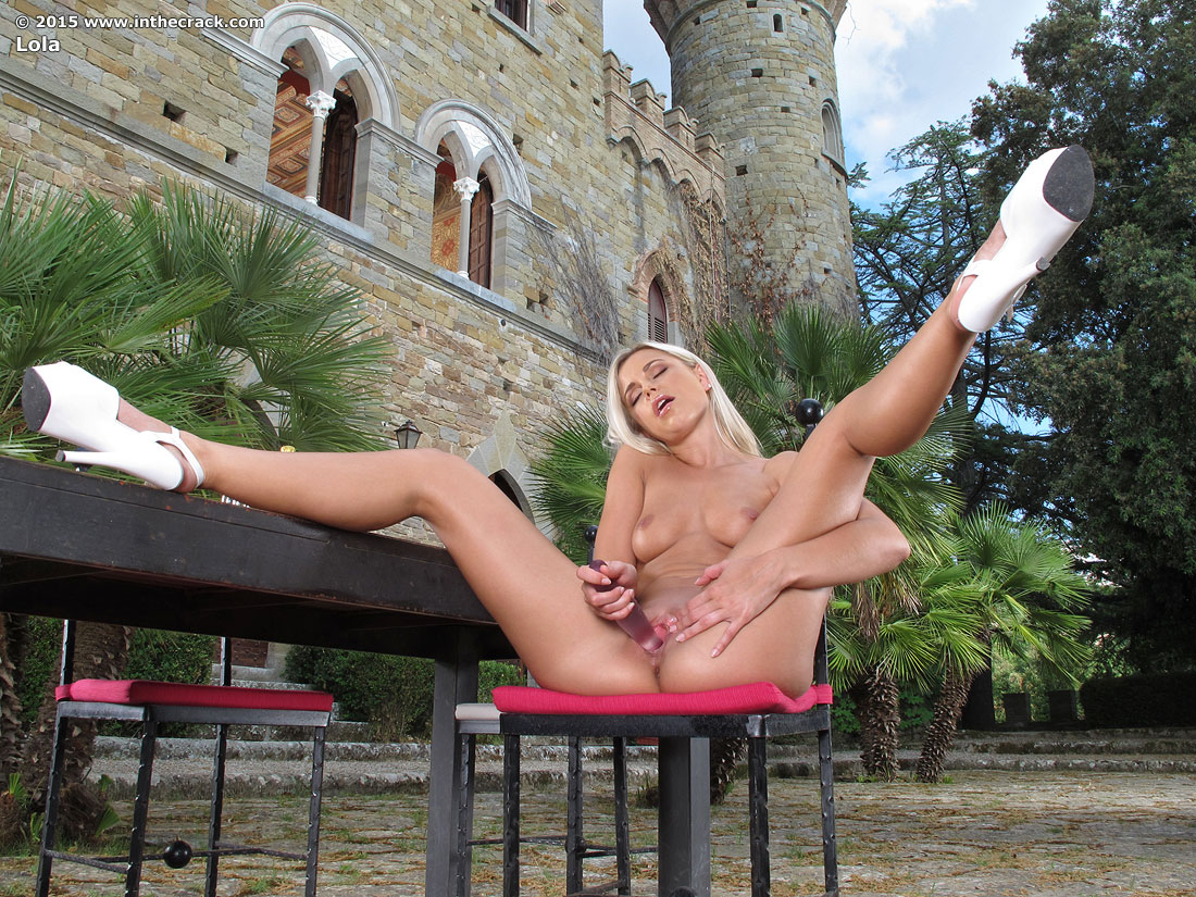 Blonde kneeling outdoors
